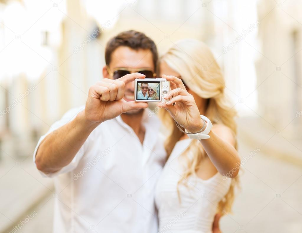 Summer holidays, travel, vacation, tourism and dating concept - travelling  couple taking photo picture with camera — Photo by Syda_Productions