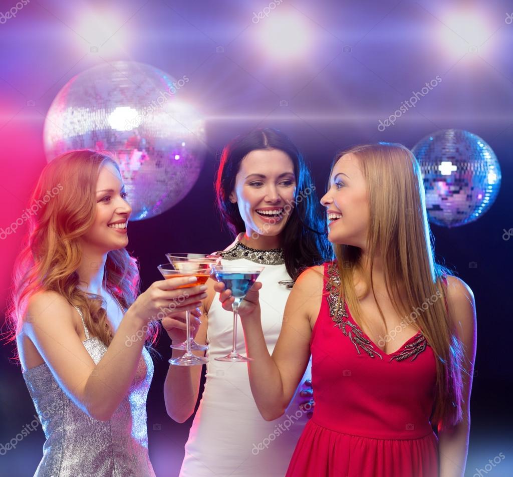 tres mujeres sonrientes con cócteles y bola de discoteca — Foto de ...