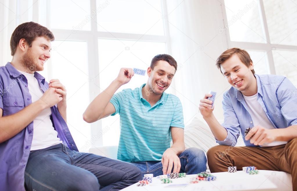 Tres sonrientes amigos hombres jugando a las cartas en su - Juegos para 3 personas en casa ...