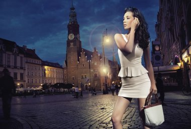 Sexy young beauty posing over night city background
