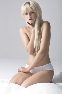 Portrait of Fresh and Beautiful blonde woman on bed