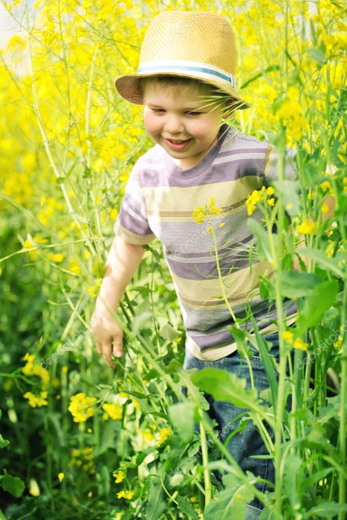 Smiling kid running among the canola flowers