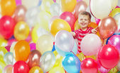 Laughing boy playing among the baloons
