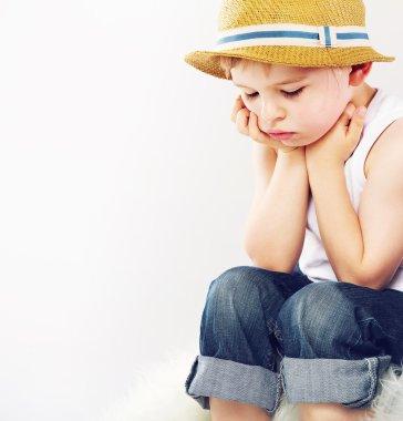 Sad boy with his straw hat