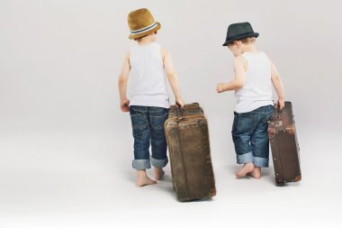 Two cute brothers leaving with their suitcases