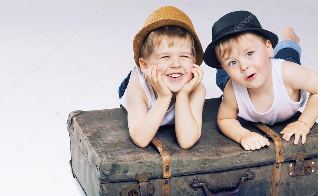 Two cute brothers lying on luggages