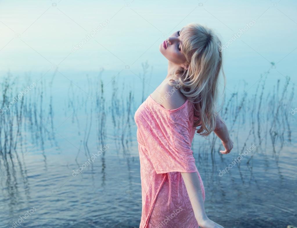 Sensual blonde girl enjoying cold lake water