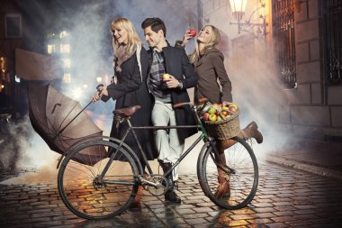 Three friends, apples and bicycle