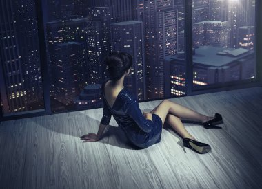 Art photo of the girl in the apartment in the skyscraper