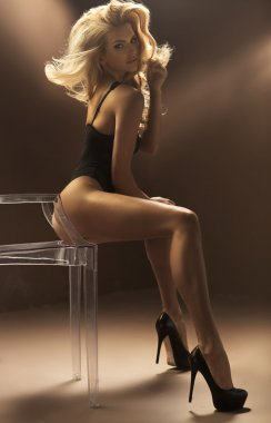 Sexy blonde woman sitting on crystal chair