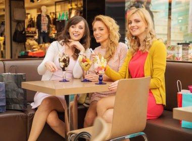 Three smiling girlfriends having the break time