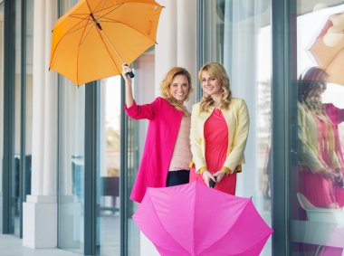 Cheerful ladies posing with the umbrellas