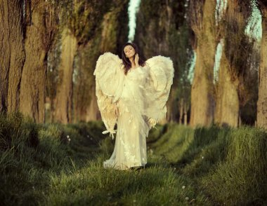 Wonderful female angel walking across the forest