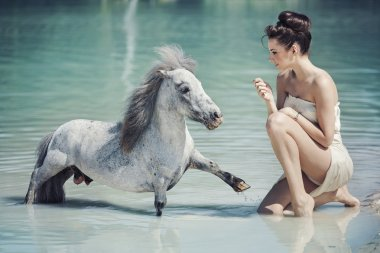 Alluring woman playing with the pony in the pool