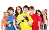 Fotografie usměvavý chlapec s dalekohledem ve skupině