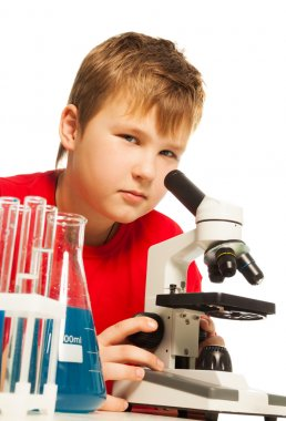 Cute boy in the lab looking through microscope with test tubes around stock vector