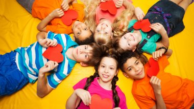 Group of kids laying with red hearts