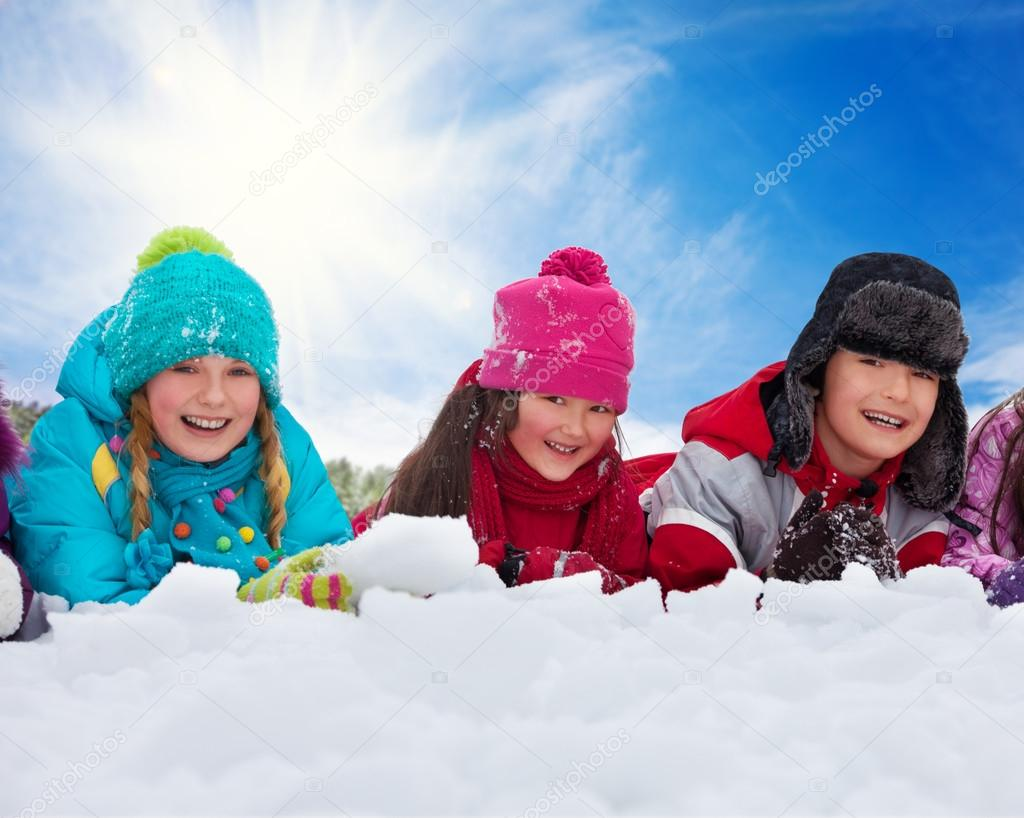 Three kids laying in snow