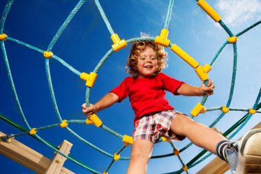 Happy little three years old child boy sitting on the web on playground and smiling ready to jump stock vector