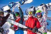 čtyři přátelé drží snowboardy a lyže