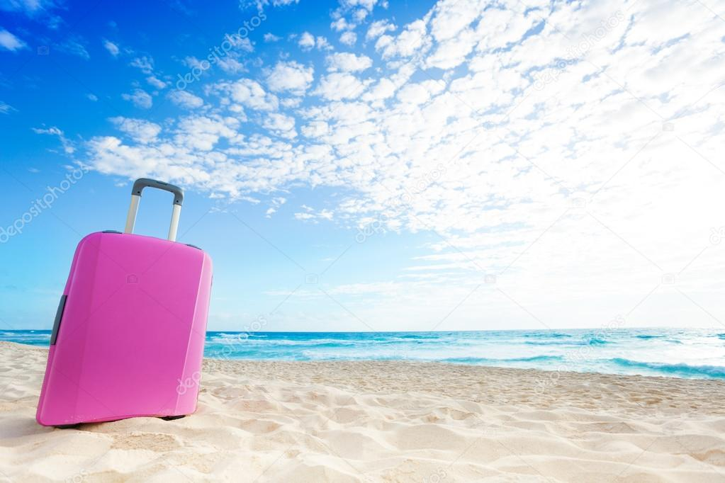 Pink baggage bag on the beach