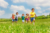 Fotografie Running kids in green field during summer