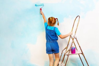 Girl paints wall