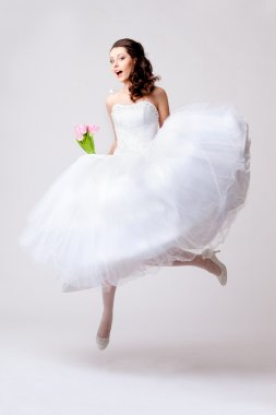 Beautiful bride jumping in studio