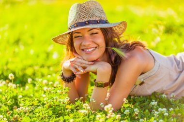 Happy beautiful woman wearing hat lying on grass stock vector