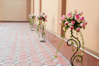 Flower bouquets in vases near a wall