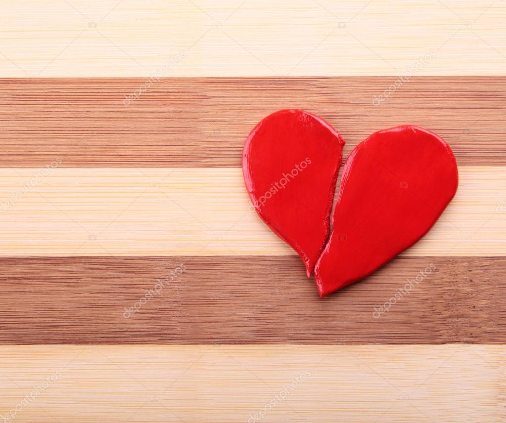 Broken heart on a wooden texture