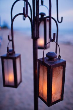 Lantern on the beach in sunset