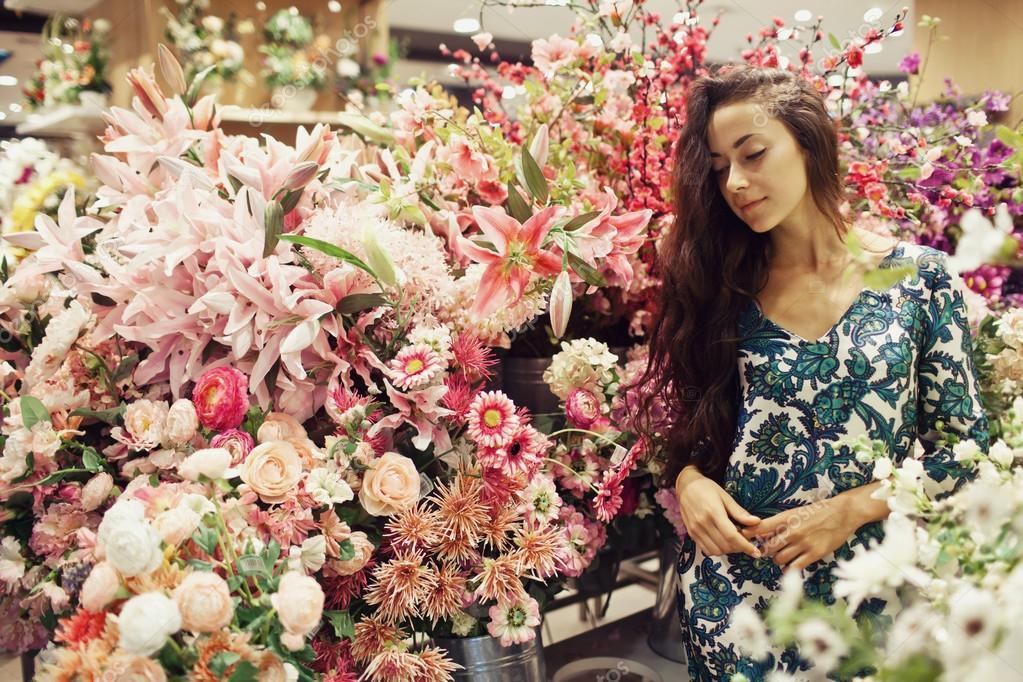 giovane e bella donna comprare fiori al mercato foto