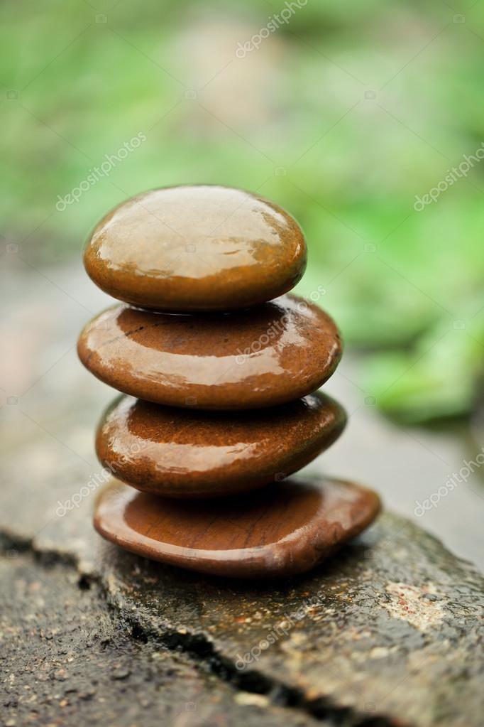 Stones pyramid near river symbolizing zen, harmony, balance.