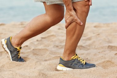 Cramps in leg calves or sprain calf on triathlete runner. Sports injury concept with running man.