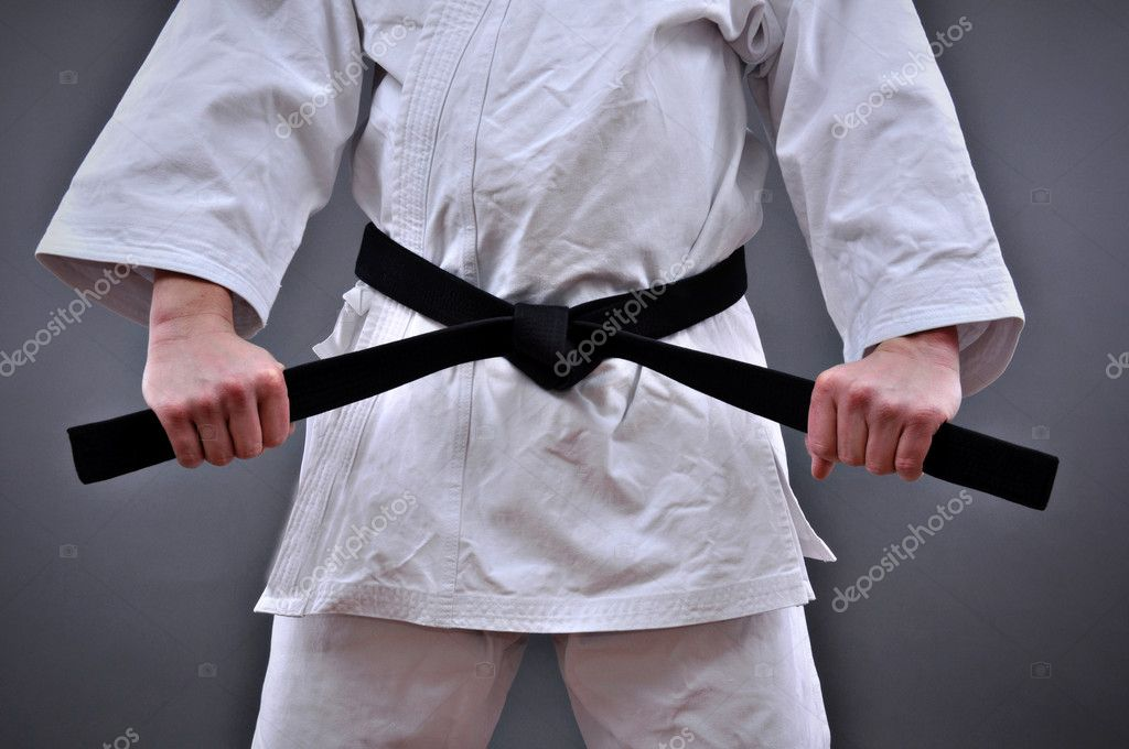 Man in martial arts uniform holding his black belt with both hands