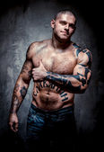 Muscular young man with many tattoos showing thumb up