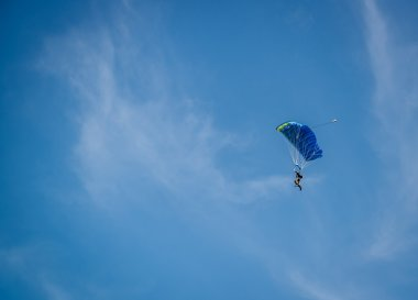 Parachutist over sky background