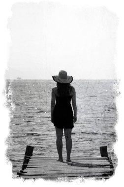 Grunge image of woman waiting on dock