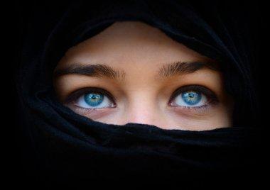Beautiful blue woman eyes behind black scarf looking up