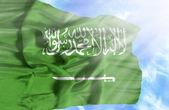 Saudi Arabia waving flag against blue sky with sunrays