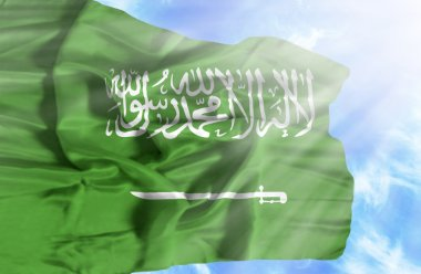 Saudi Arabia waving flag against blue sky with sunrays