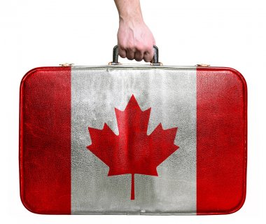 Tourist hand holding vintage leather travel bag with flag of Can