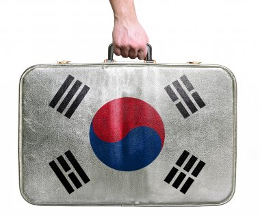 Tourist hand holding vintage leather travel bag with flag of Sou