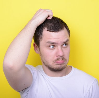 Portrait of funny cluelles man against yellow background