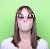 Ritratto di ragazza con gli occhiali retrò rendendo il palloncino con bolla g