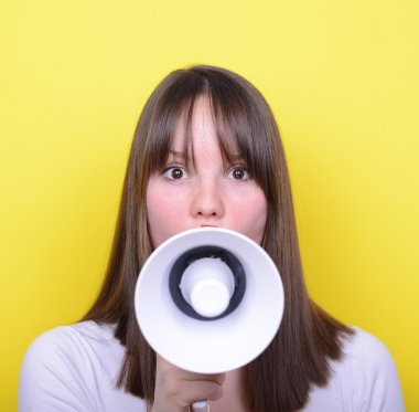 Portrait of young woman shouting with a megaphone against yellow