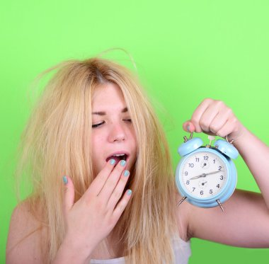 Portrait of sleepy young female in chaos holding clock against g