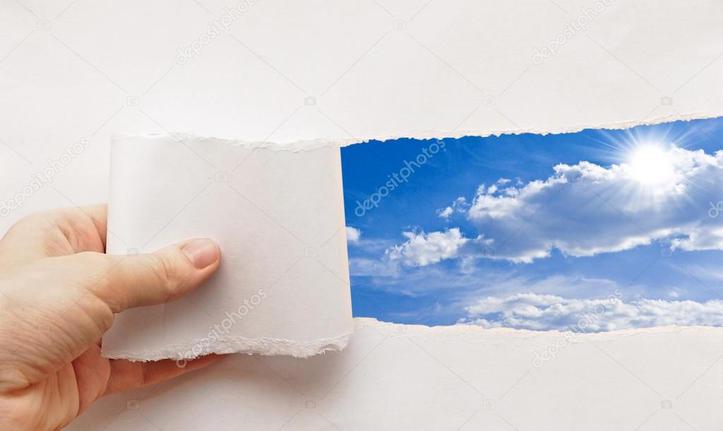 Blue sky behind torn paper