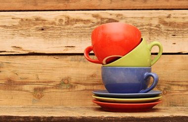 Colorful coffee mugs over an grunge wooden background